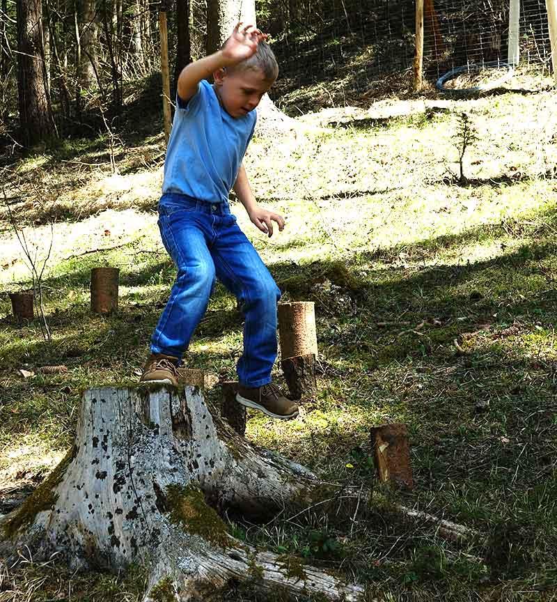 junge mit blauem polo und jeans beim spielen im wald